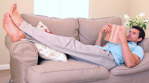 Man lying on couch falling asleep while reading Footage