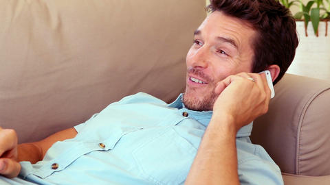 Man lying on couch answering his phone Footage