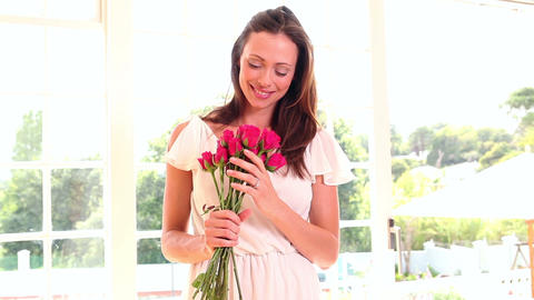 Pretty woman smelling bouquet of roses Footage