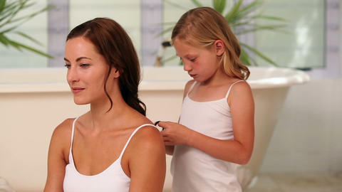 Little girl plaiting her mothers hair in the morni Footage