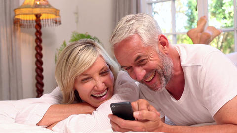 Couple lying on bed using smartphone together Footage