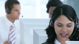 Smiling businesswoman in a call center with her te Footage