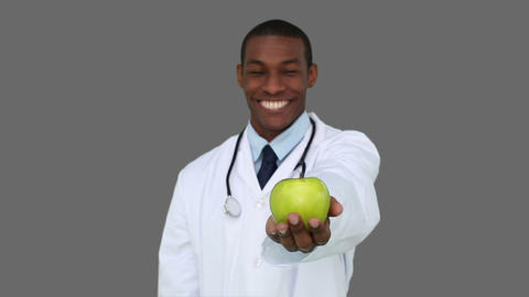 Happy young doctor showing camera an apple Footage