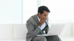 Happy businessman using a laptop celebrating a suc Footage