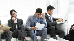 Business people sitting on a sofa waiting in offic Footage