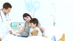 Doctor taking little boys pulse in hospital Footage