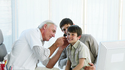 Doctor Examining Little Boys Ears In Office stock footage