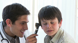 Close up of doctor examining little boys ears Footage