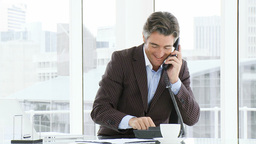 Happy businessman talking on phone in office Footage