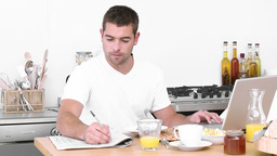 Man working with a laptop in the kitchen and havin Footage