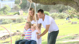Family swinging in a park Footage