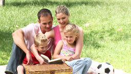 Family reading a book in a park Footage