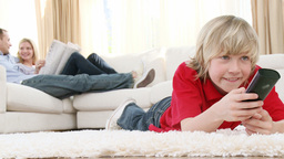 Boy watching television on floor with his parents  Footage