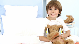 Little boy and teddy bear listening to music on be Footage