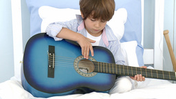 Little boy playing guitar on bed Footage