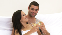 Couple drinking champagne in bed Footage