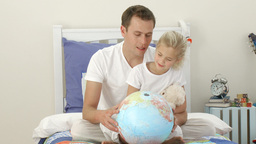 Father and daughter looking at a terrestrial globe Footage
