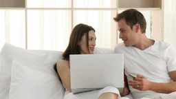 Couple using a laptop in the bedroom Footage