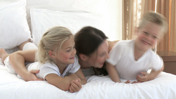 Attractive mother and children playing in bed Footage