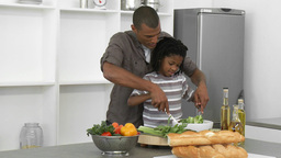 AfroAmerican father and son preparing a salad at h Footage