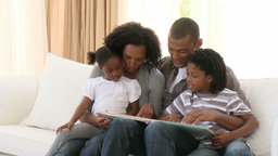 AfroAmerican parents and children reading a book i Footage