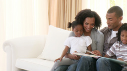 AfroAmerican family reading a book in the living-r Footage