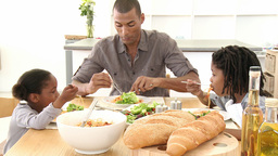 Father and children eating pasta and salad in the  Footage