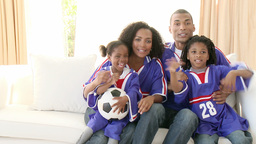 Excited AfroAmerican family watching a football ma Footage