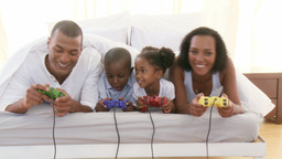 AfroAmerican family playing video games in the bed Footage
