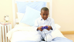 AfroAmerican little kid playing video games in his Footage