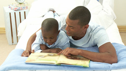 AfroAmerican little boy and his father reading a b Footage