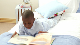 AfroAmerican smiling little boy reading in bed Footage