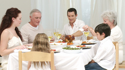 Parents, children and grandparents having dinner at home Live Action