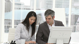 Two businesspeople working seriously at a computer Footage