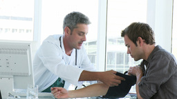 Male doctor examining a patients blood pressure Footage