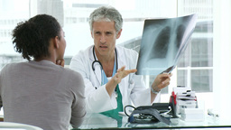 Male doctor and his patient looking at lungs Xray Footage