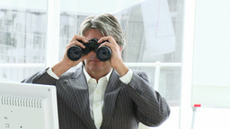Competitive male executive looking through binocul Footage