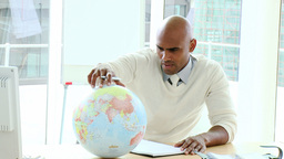 Ethnic businessman looking at a terrestrial globe Footage