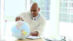 Ethnic businessman looking at a terrestrial globe Live Action