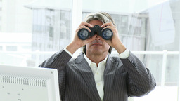 Mature businessman looking through binoculars Footage