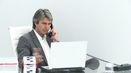 Serious executive on phone working at a laptop Footage