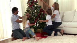 Montage of a family decorating a christmas tree Animation