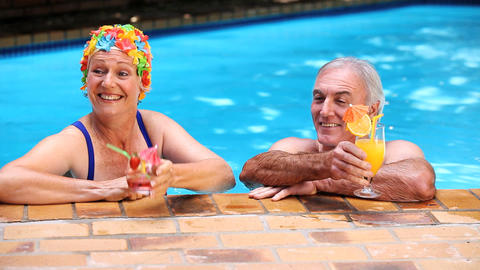 Happy mature couple relaxing in the swimming pool Footage