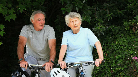 Elderly couple walking with their bikes Footage