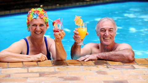 Happy old couple relaxing in the swimming pool Footage