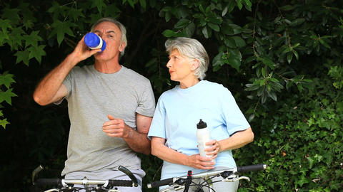 Elderly couple with bikes taking a break to drink Footage