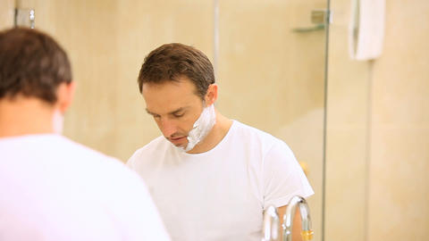 Handsome man shaving his beard in front of a mirro Footage