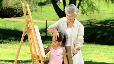 Young child painting a canvas with grandmother Footage