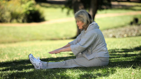 Old woman doing warm up sitting on the grass Footage