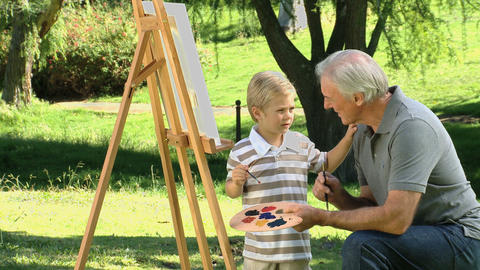 Young child painting a canvas with grandfather Footage